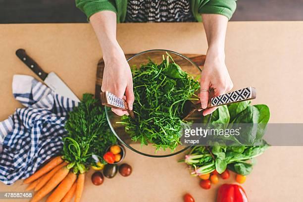 Jovem mulher fazendo salada fresca
