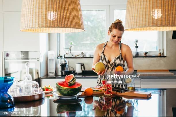Jeune femme faisant des jus de fruits et salade de fruits dans la cuisine