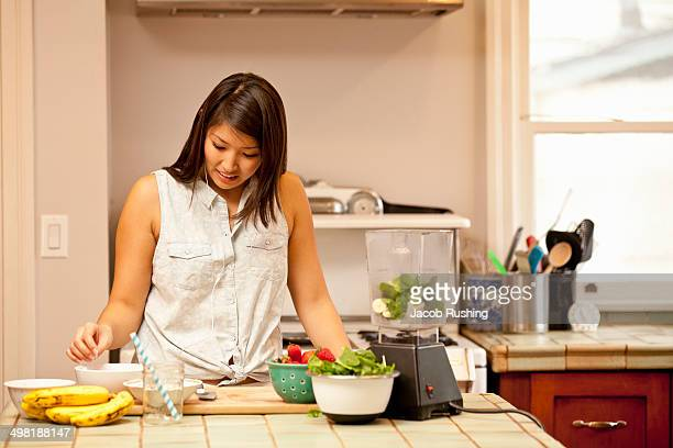 Young woman making green smoothie in kitchen