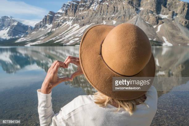 Young woman making heart shape finger frame on mountain lake