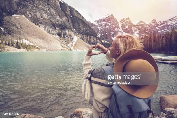 Young woman making heart shape finger frame on mountain lake