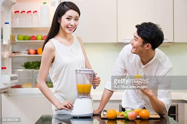 Young woman making orange juice for husband