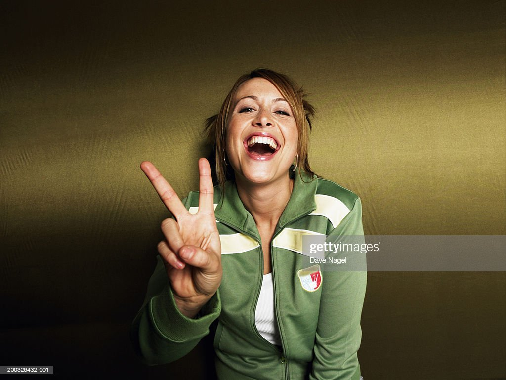 Young woman making peace sign, smiling, portrait, close-up
