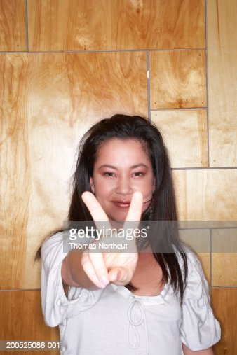 Young woman making peace sign, smiling, portrait : Stock Photo