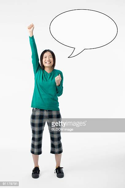 Young woman making pose and speech bubble on wall, studio shot