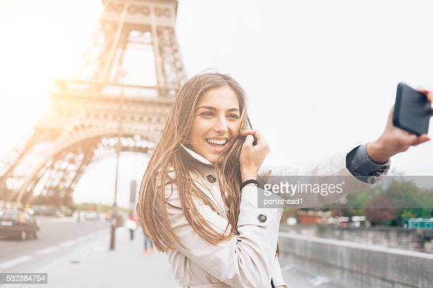 Young woman making selfie in front of Eiffel tower, Paris