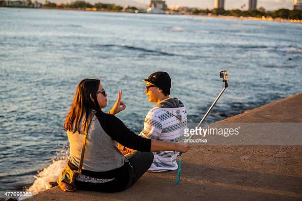 Young woman making selfie sitting on the beach