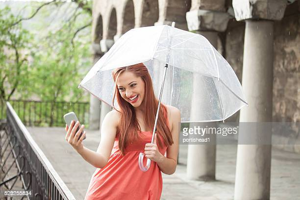 Young woman making selfie with umbrella under the rain