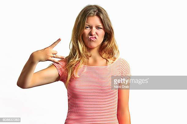 Young woman making silly face and hand sign