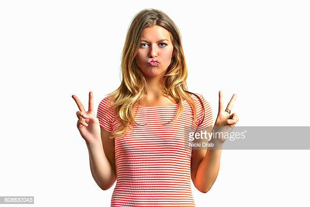 Young woman making silly face and peace sign
