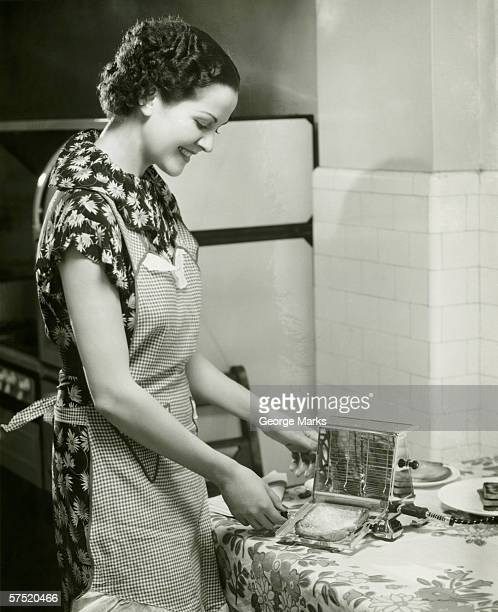 Young woman making slice of toast, (B&W), portrait