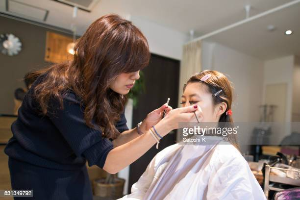 Young woman making up in beauty salon
