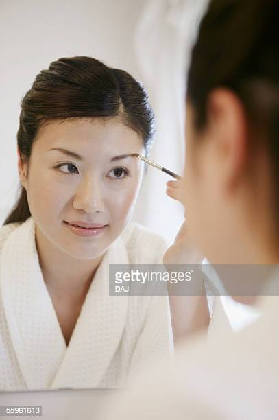 Young Woman Making Up In Front Of The Mirror