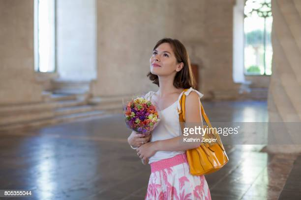 Young woman marvelling at Spanish Gothic architecture, holding a bouquet of flowers