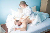 Young woman massage her husband in bed