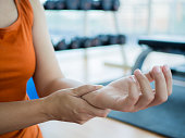 Young woman massaging her wrist after working out or injured hand during careless sport practice with fitness equipment background.