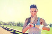 Young woman measuring heart rate after running