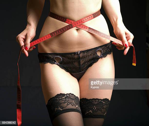 Young Woman Measuring Tummy With Tape Measure