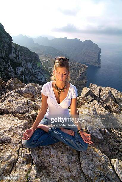 young woman meditates ath the top of a hill
