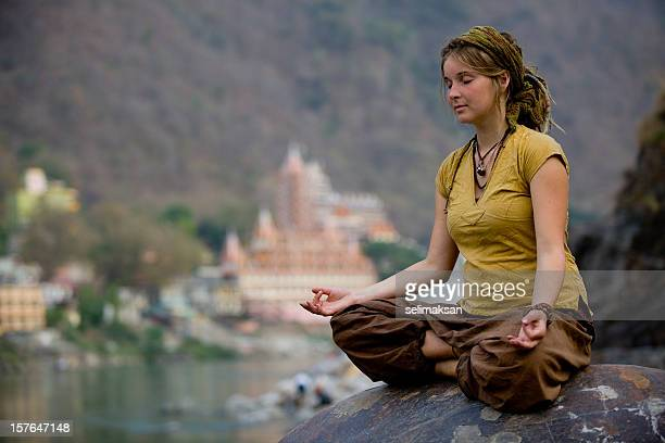 Young woman meditating by ganges river in rishikesh
