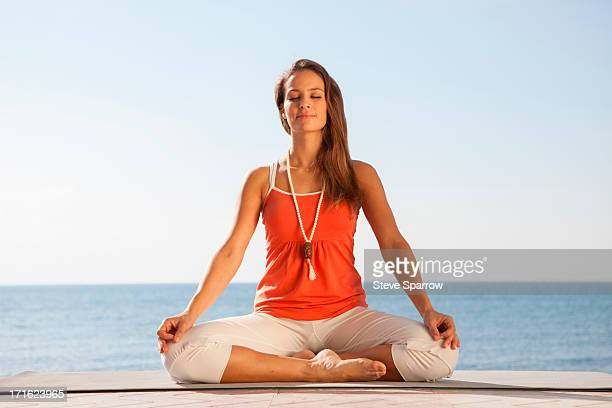 Young woman meditating by sea