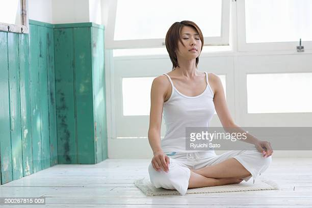Young woman meditating by window