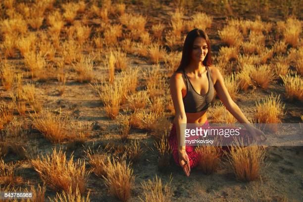 Young woman meditating in a meadow