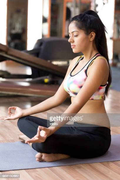 Young woman meditating on exercise mat