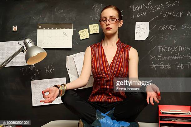 Young woman meditating on office desk