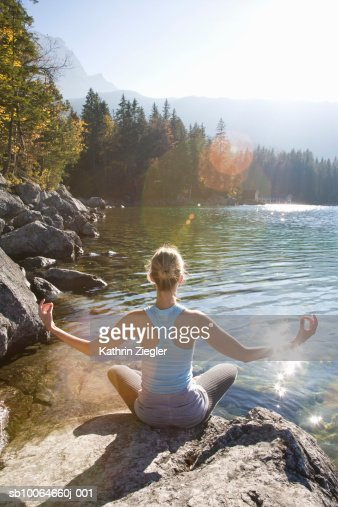 Young woman meditating on rock by lake, rear view : Stock Photo