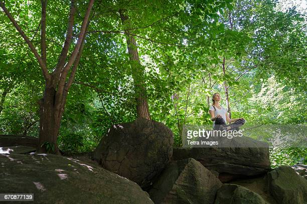Young woman meditating on rocks in woodland