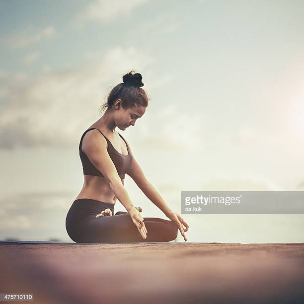 Young woman meditating outdoors on a rooftop at sunset