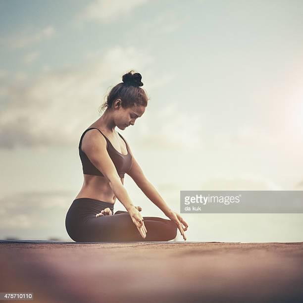 Giovane donna che meditating all'aperto su un tetto al tramonto