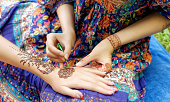 young woman mehendi artist painting floral ornament henna on the hand