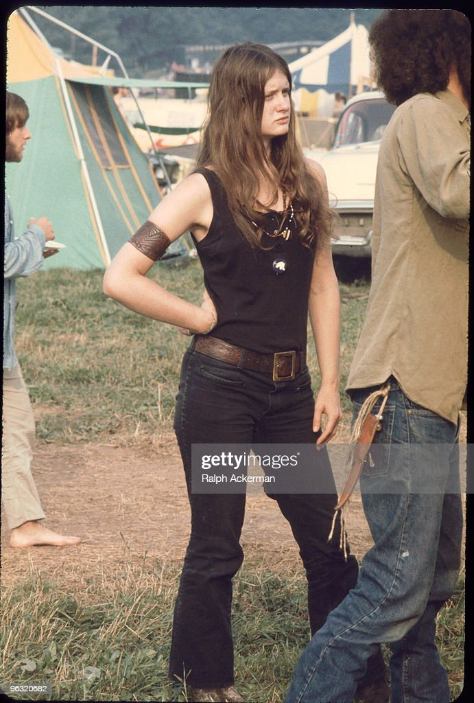 Young woman member of the White Panthers a group formed to support the work of the Black Panthers stands aside as young man sets up a tent at the...