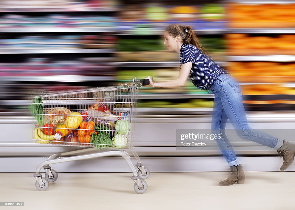 Young woman messing around in supermarket : Stock Photo