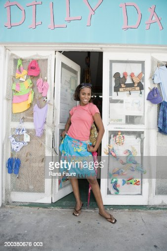Young woman modeling sarong in front of gift shop, portrait