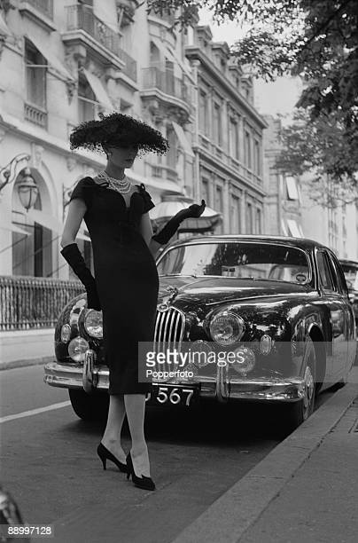 A young woman modelling an outfit consisting of a threequarterlength dress high heeled shoes hat and gloves 1957