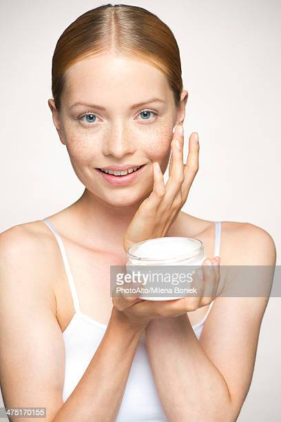 Young woman moisturizing face