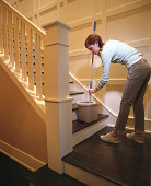 Young woman mopping floor in stairwell