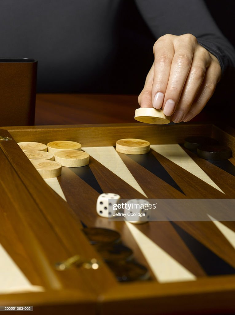 Young woman moving backgammon piece : Stock Photo
