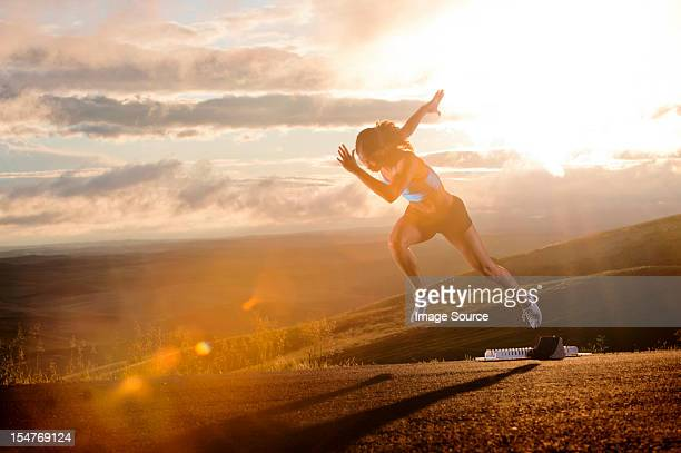Young woman moving off starting blocks in rural setting