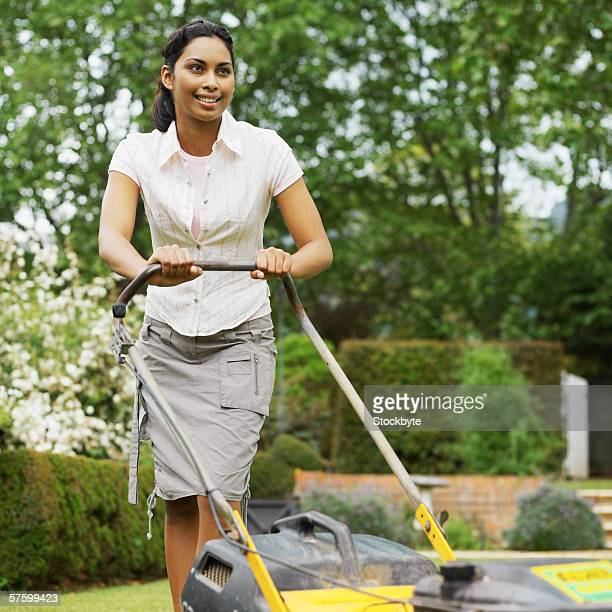 Young woman moving the lawn