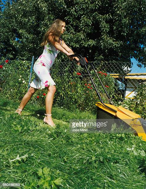 Young Woman Mowing Lawn