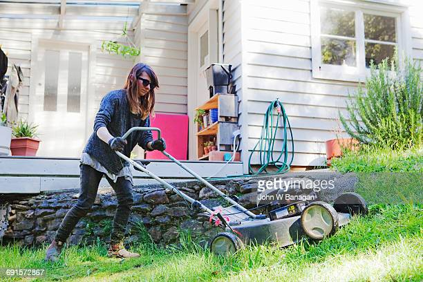 Young woman mowing lawn.Australia