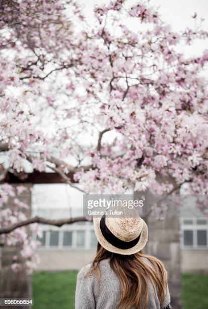 Young woman near the blooming tree in spring time