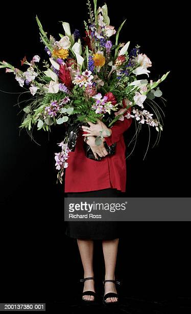 Young woman obscuring face with bouquet of flowers