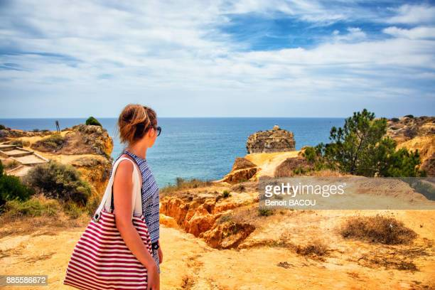 Young woman observing the sea from the cliffs of the cove of Praia de Galapinhos, Setubal, Lisbon area, Portugal