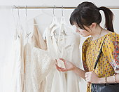 Young woman observing wedding dress in shop