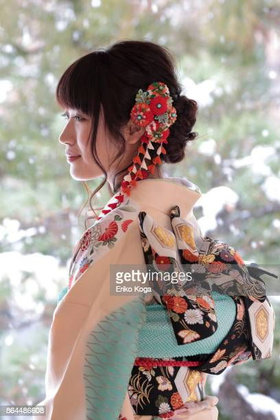 Young woman of coming‐of‐age ceremony attached hair ornament in front of snowy Japanese garden